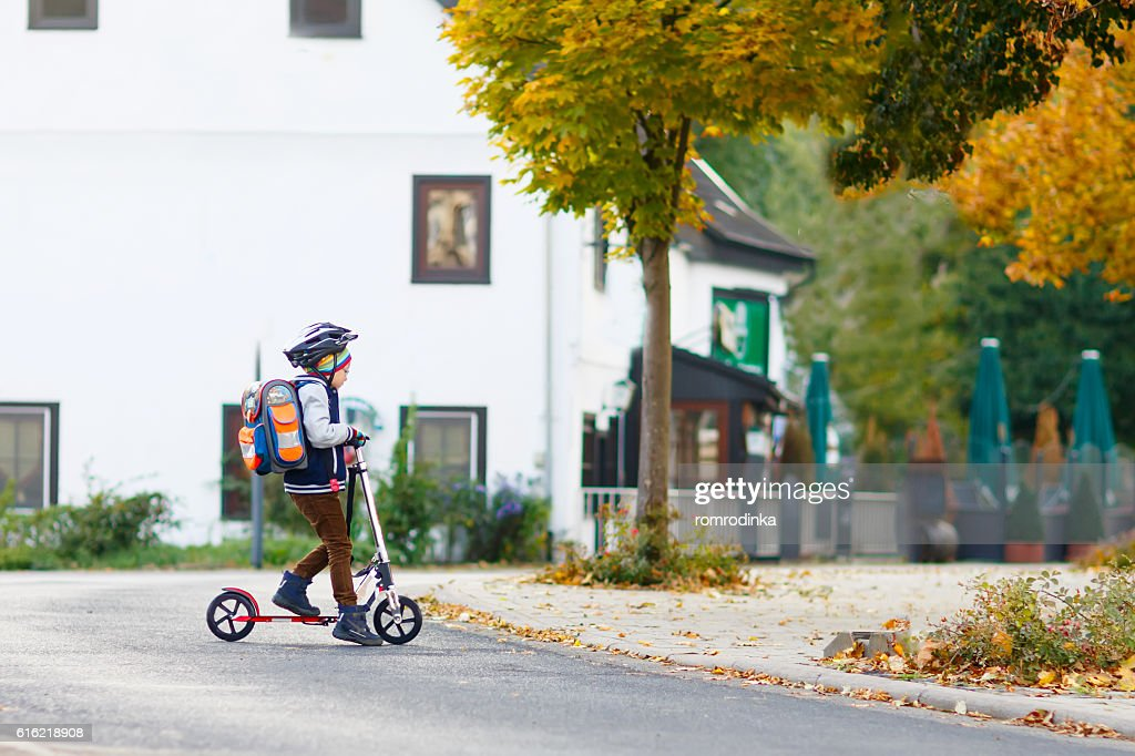 Little kid boy in helmet riding with scooter through city : Foto stock