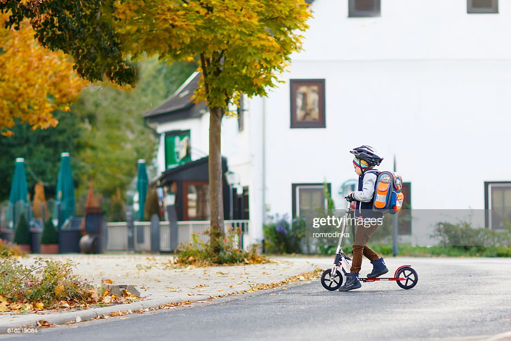 Little kid boy in helmet riding with scooter through city : Stock-Foto