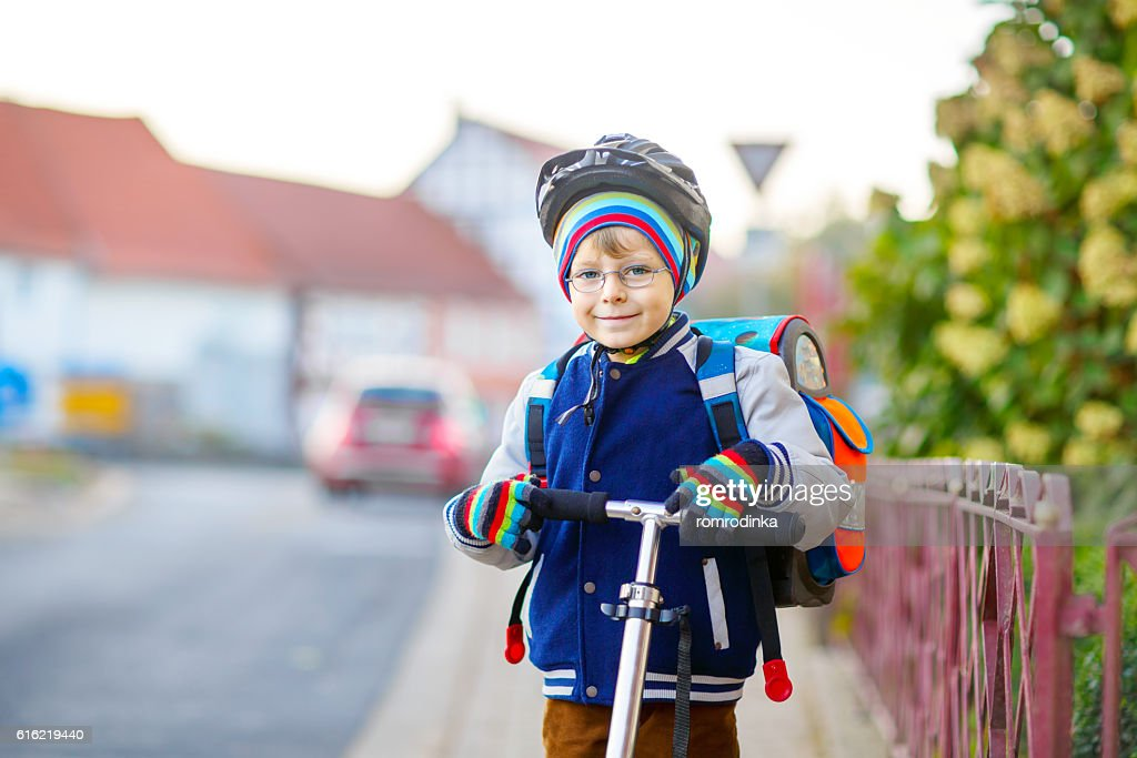 Little kid boy in helmet riding with scooter through city : Stock Photo