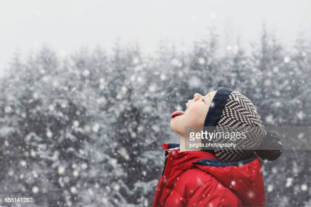 little kid catching snowflakes with his tongue - red hat stock pictures, royalty-free photos & images