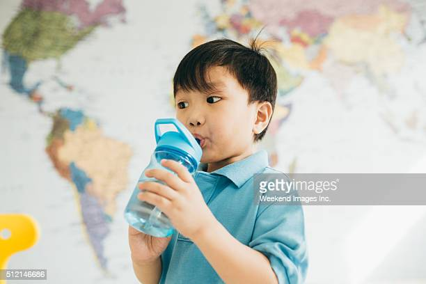 little kid drinking water - asian drink stock photos and pictures