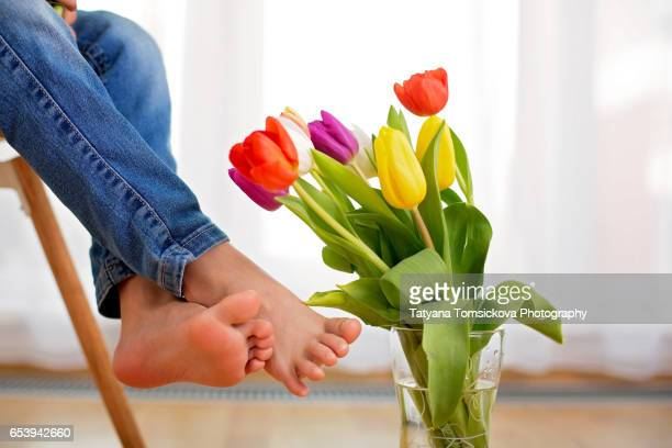 Little kid fee, child sitting on a chair at home, vase with tulips next to them, back light