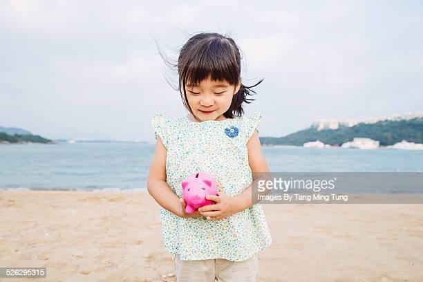 Little kid holding a piggy bank on beach