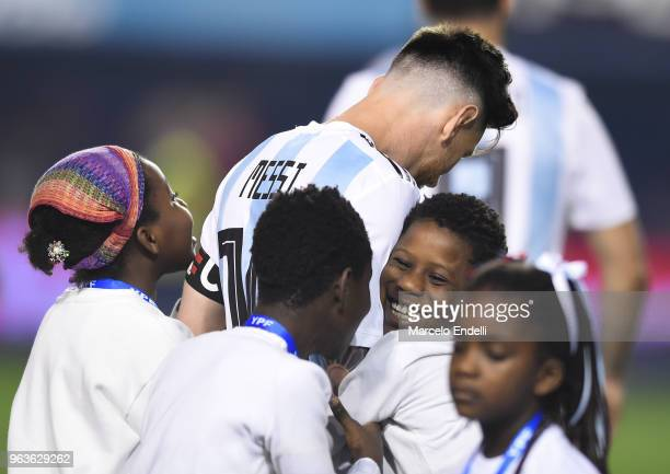 A little kid hughs Lionel Messi of Argentina prior an international friendly match between Argentina and Haiti at Alberto J Armando Stadium on May 29...