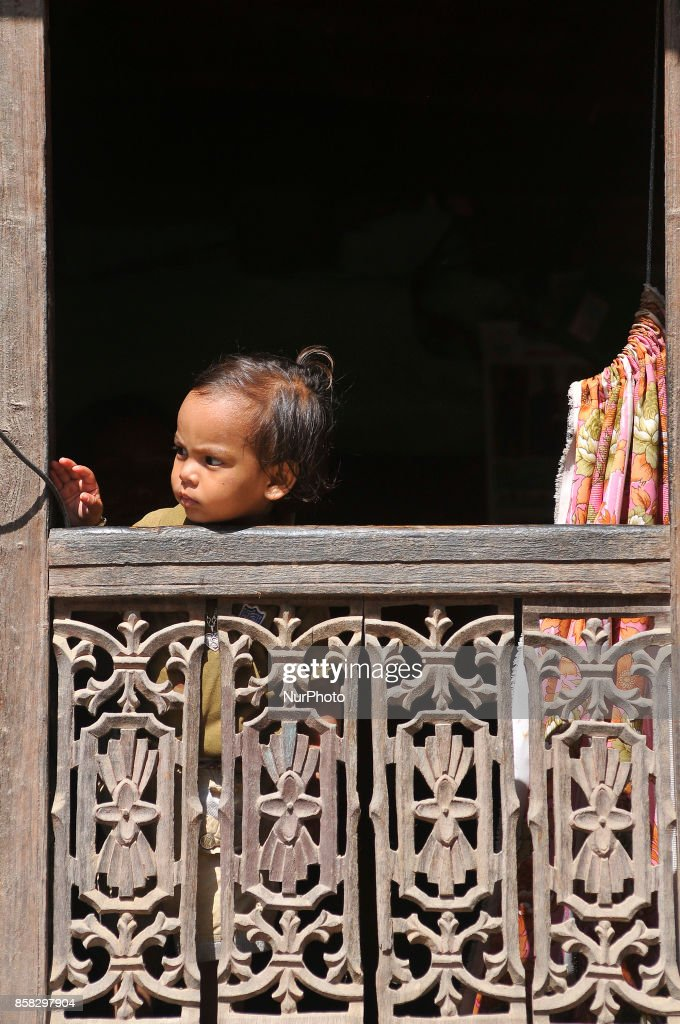 A Little kid observing festival as Locals carry as well as rotates top part of a chariot of Lord Narayan across the streets of Hadigaun during Lord Narayan jatra festival in Hadigaun, Kathmandu, Nepal on Friday, October 06, 2017. Once in a every year right after Dashain Festival this festival celebrates. The Narayan Jatra Festival of Hadigaun is a unique Festival in the capital involving three circular bamboo structures, above which an idol of the Lord Narayan in placed, and then rotated by two people standing below.