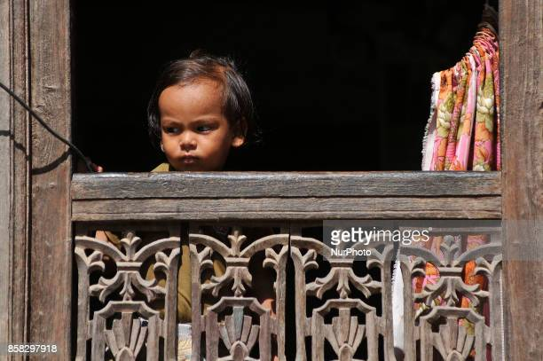 A Little kid observing festival as Locals carry as well as rotates top part of a chariot of Lord Narayan across the streets of Hadigaun during Lord...