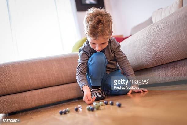 Little kid playing with marbles