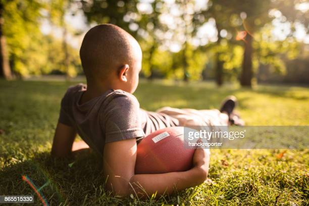 little kid resting with football ball