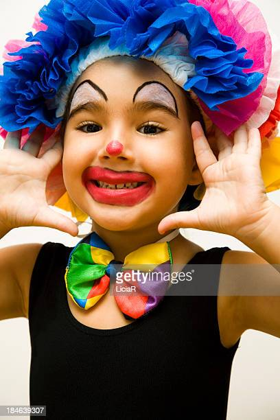 A little kid who is dressed up like a clown