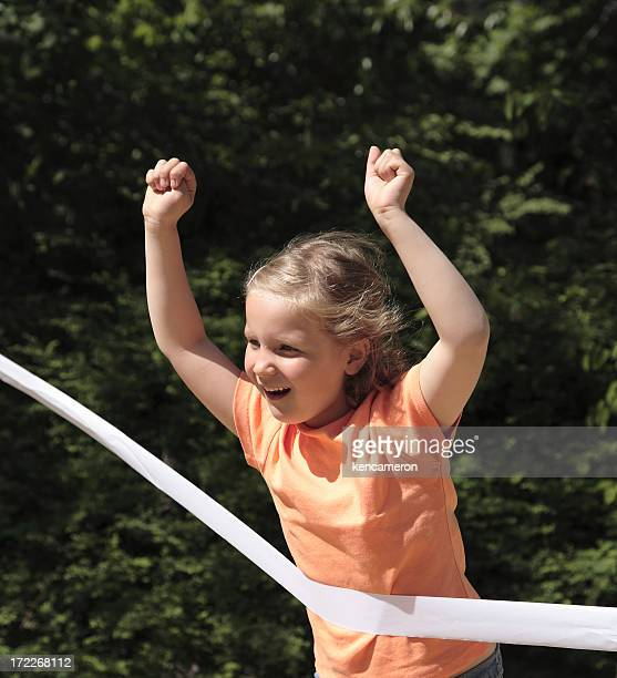 A little kid winning a race and tearing a white ribbon