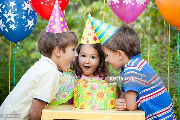 3 little kids at a birthday party all excited about the gift