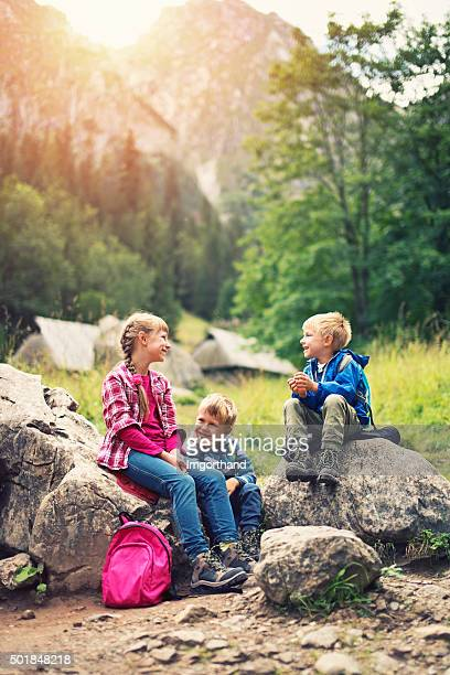 Little kids hikers resting in mountains.