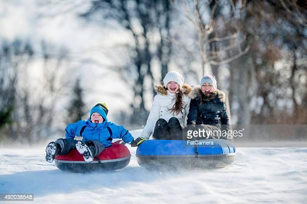 Kleine Kinder Inneren Tubing an einem sonnigen Wintertag