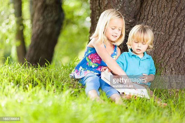 Little kids reading under a tree