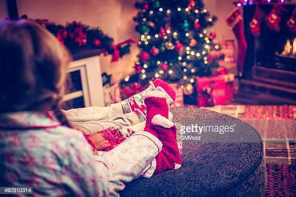 Enfants assis en chaussettes d'hiver avec l'arbre de Noël
