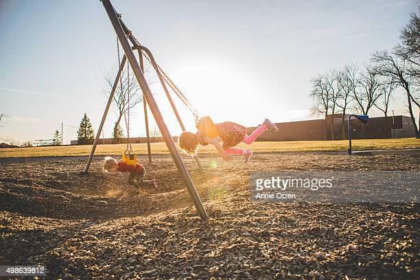 Little kids swinging on swing set on stomach
