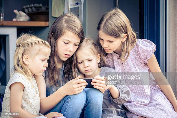 little kids watching cartoons on the mobile phone. - petite teen girl stock photos and pictures