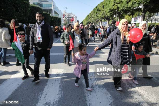 Little kids with their parents hold red balloons and flag of Palestine as they attend the celebrations of the 9th held on avenue Habib Bouguiba in...