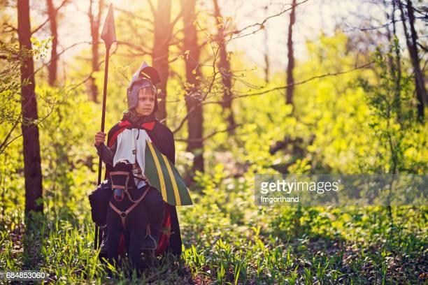Der kleine Ritter auf Spielzeugpferd im Wald