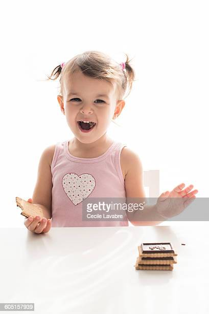 Little laughing girl eating biscuits