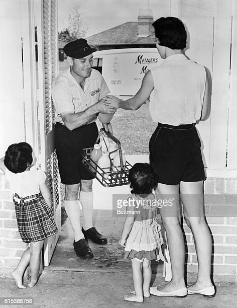 1955 ORIGINAL CAPTION READS Little Laura with her mother Mrs Maurice Schermann and sister Linda fascinated at the sight of Herman Malone milkman in...