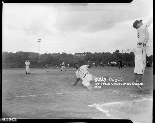 Little League baseball player Fireman's Department Store team sliding into third base at Kennard Field with Terrace Village in distance as third...