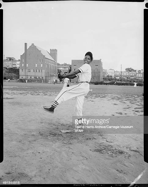 Little League baseball player pitching from pitcher's mound on Ammon Recreation Center field Pittsburgh Pennsylvania circa 19501970