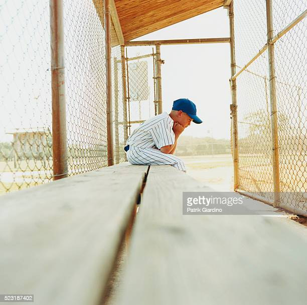 little league baseball player sitting alone on bench - sports dugout stock pictures, royalty-free photos & images