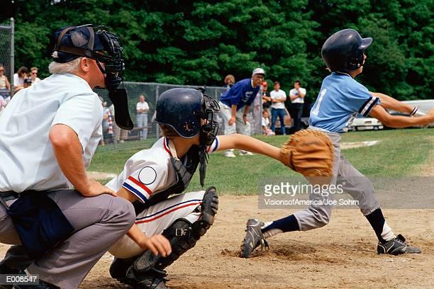 Little League batter swinging at ball