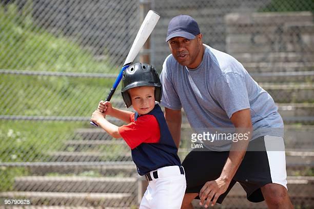 Little League Coach Helping Boy With Batting