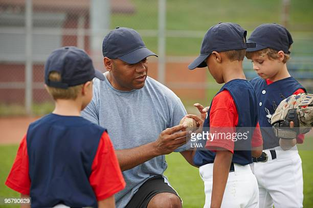little league coach teaching boys to pitch - little league stock pictures, royalty-free photos & images