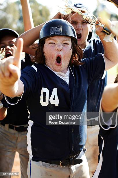 A little league player celebrates with trophy.