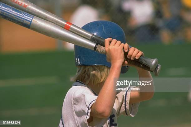 Little League Player Swinging Two Aluminum Bats