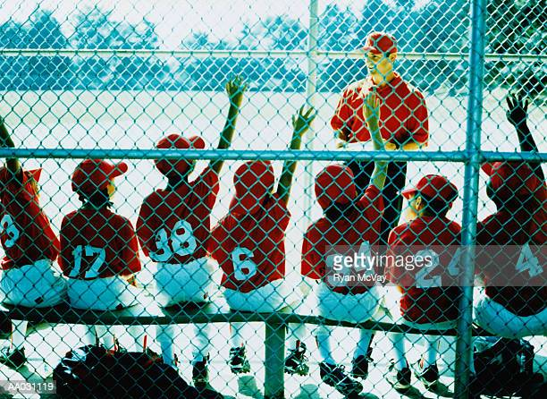 little league team and coach in dugout - baseball team stock pictures, royalty-free photos & images