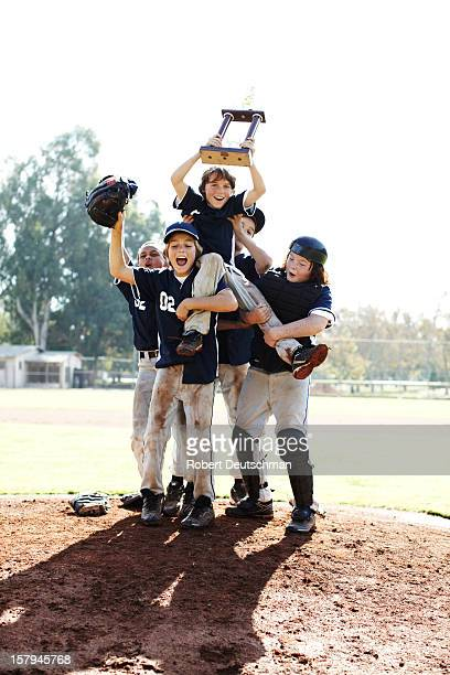 Little league team celebrating with trophy.