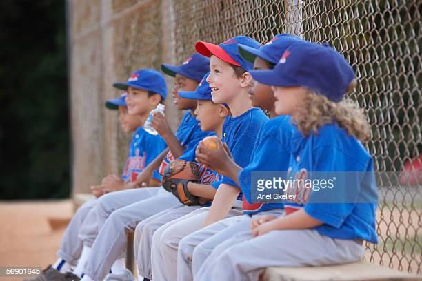 Little League team sitting on bench