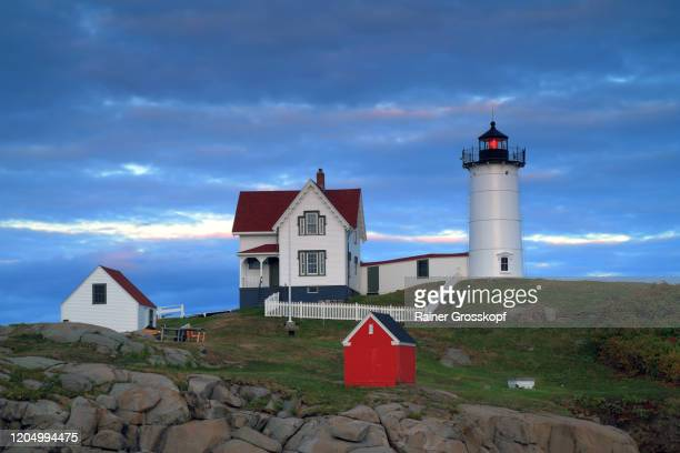 little lighthouse on a small island at sunset - rainer grosskopf stock pictures, royalty-free photos & images