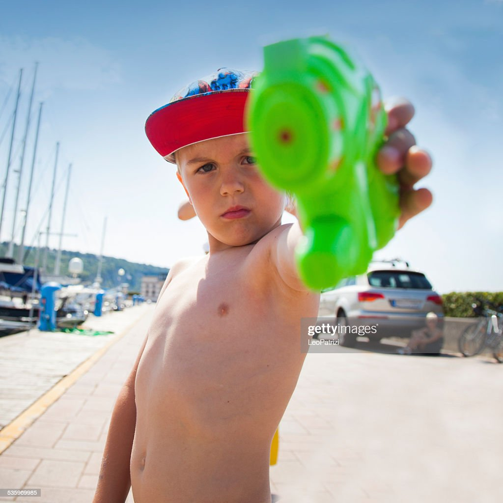 Little man playing with a water gun : Stock Photo