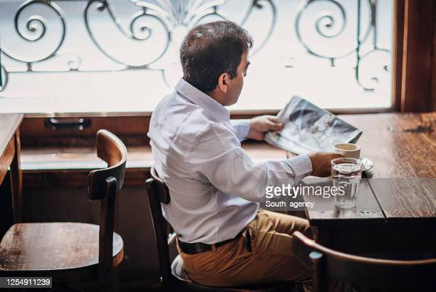 little man reading newspaper in cafe - dwarf man stock pictures, royalty-free photos & images