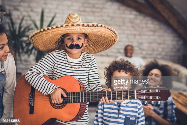 little mariachi boy playing a guitar to his family at home. - mexican hat stock pictures, royalty-free photos & images