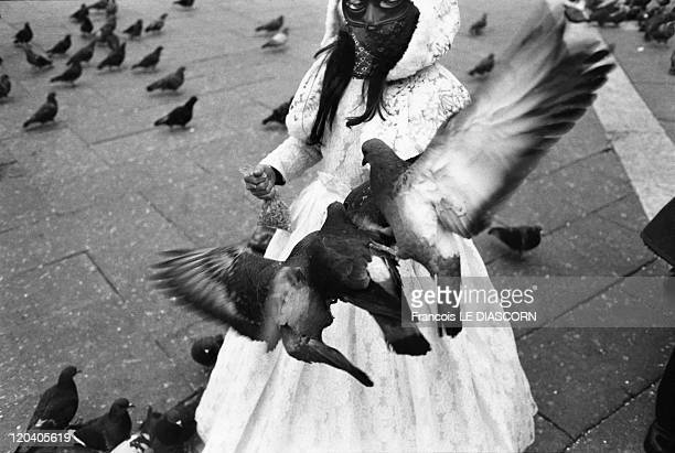 Little masked girl with pigeons in Venice Italy Little masked girl with pigeons on St Mark's Square during the Carnaval