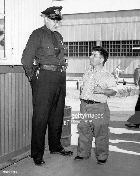 Little Men Help Make Big Airplanes L Dwight Stover right displaying his badge to Officer T H Anderson at the Goodyear Aircraft Corporation spent most...
