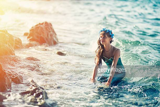 little mermaid at the shore - mermaid stock photos and pictures