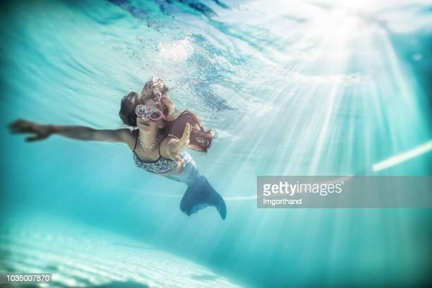little mermaid swimming underwater. - mermaid stock photos and pictures