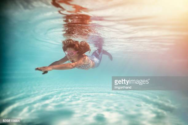 Little mermaid swimming underwater.