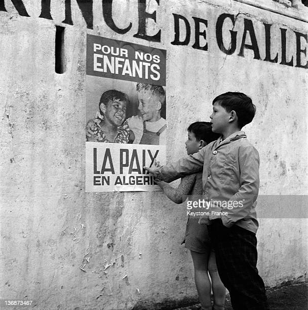 Little Muslim boys looking at a poster for peace in Algeria on the first day of the ceasefire on March 20 1962 in Algiers Algeria