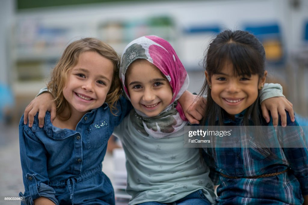Little Muslim girl and her friends enjoy a day at school together. : Stock Photo
