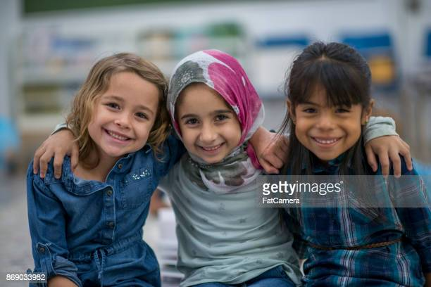 little muslim girl and her friends enjoy a day at school together. - religion stock pictures, royalty-free photos & images