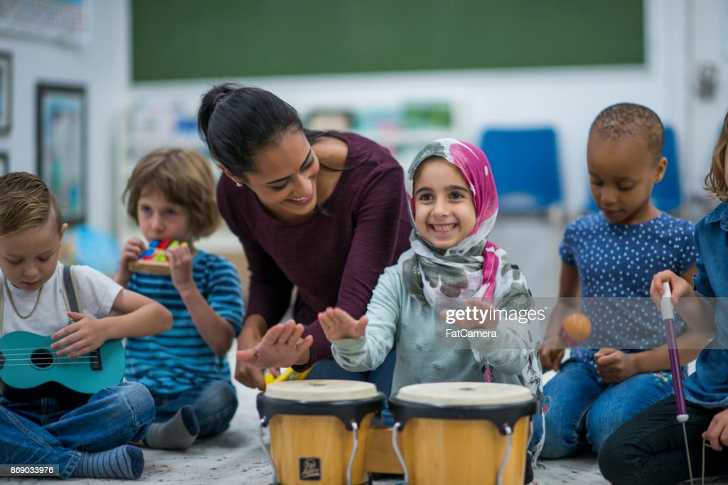 Little Muslim girl enjoy music class at school with her friends. : Stock Photo