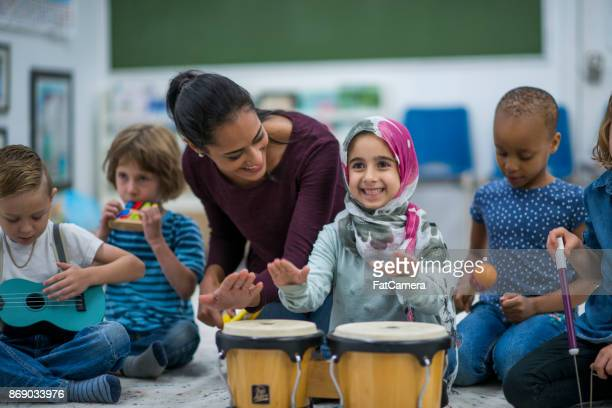 Little Muslim girl enjoy music class at school with her friends.